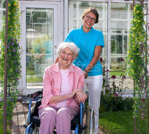 Professional carer behind happy elderly woman Stock photo © belahoche