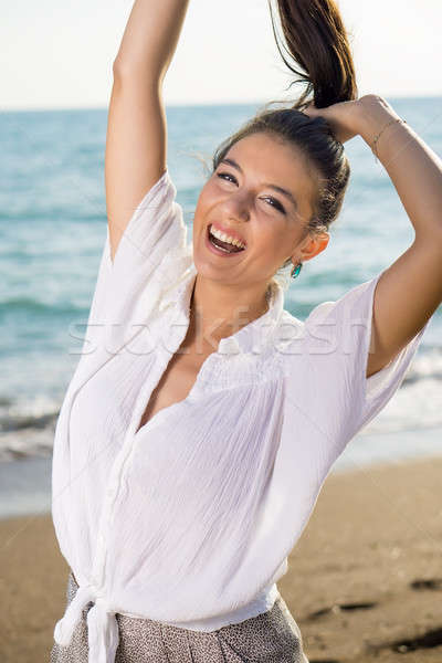 Happy Woman at the Beach Lifting her Hair Stock photo © belahoche