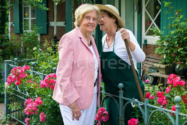 Two Senior Women Telling Secrets in Home Garden Stock photo © belahoche