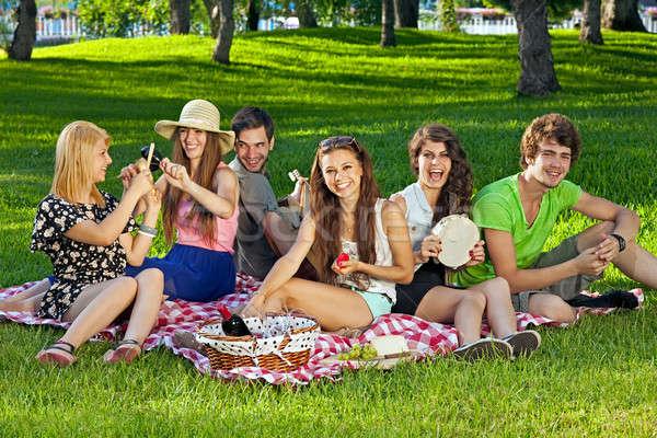 Főiskola diákok élvezi piknik park ül Stock fotó © belahoche