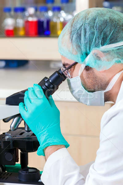 Male lab technician looking down a microscope.  Stock photo © belahoche