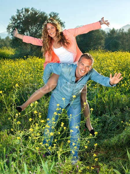 Happy lively young couple riding piggy back Stock photo © belahoche