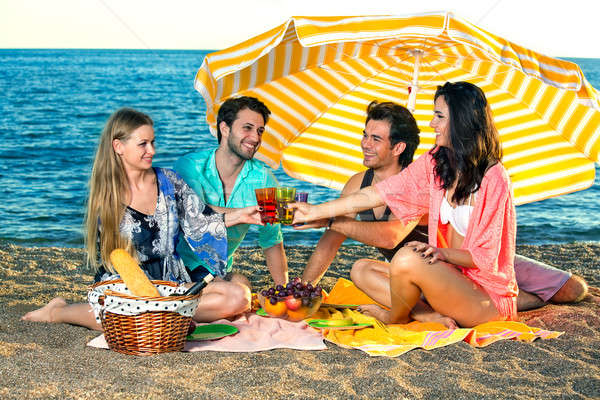 Four happy friends have a picnic on the beach Stock photo © belahoche