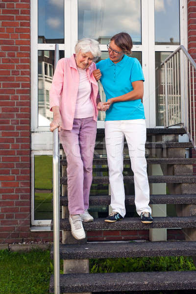 Care assistant helping a senior lady on steps Stock photo © belahoche