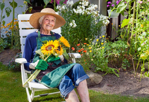 Stock photo: Old Woman Sitting on a Chair Holding Sunflowers