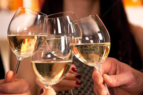 Clicking glasses with white wine.  Stock photo © belahoche