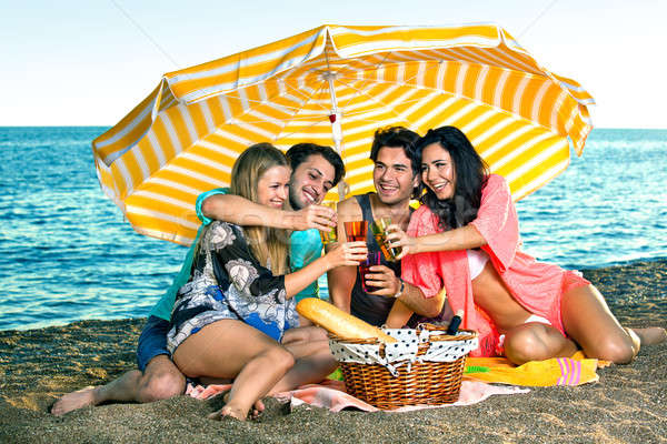 Smiling friends on vacation toast near the ocean Stock photo © belahoche