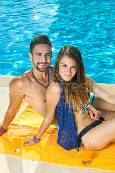 Tanned fit couple relaxing at a sunny pool Stock photo © belahoche