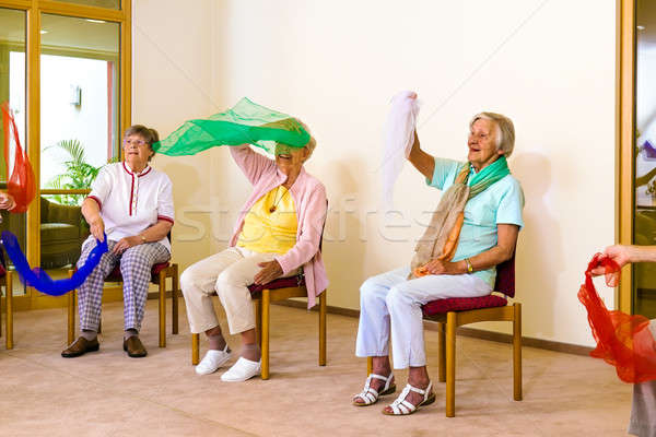 Excited women doing exercises in chairs Stock photo © belahoche
