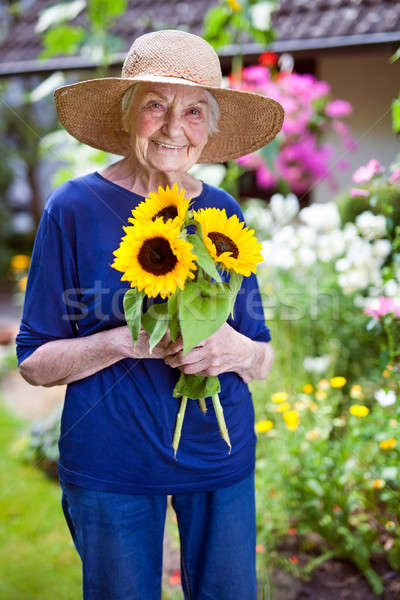 Stock photo: Happy Senior Woman Holding Pretty Sunflowers