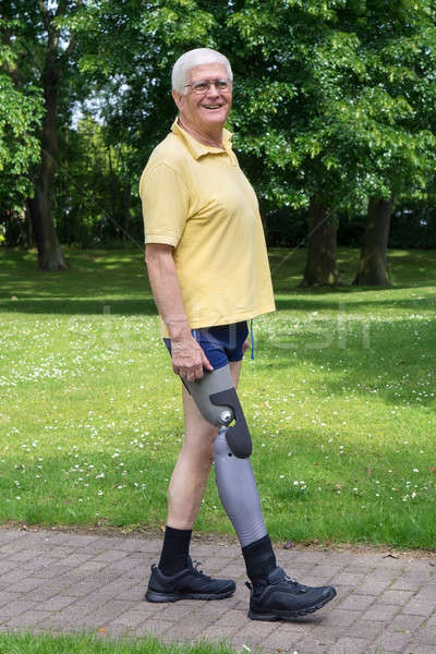 Happy older man walking with prosthetic leg Stock photo © belahoche