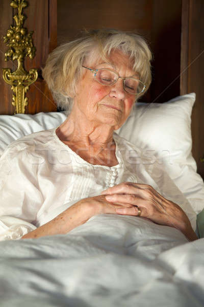 Elderly lady dozing in her bed Stock photo © belahoche