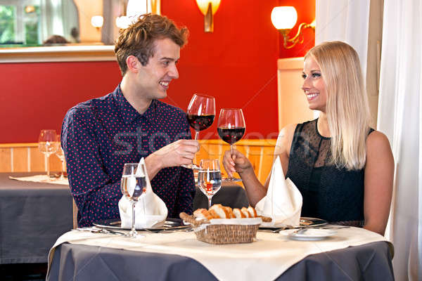 Young couple toasting each other with red wine Stock photo © belahoche