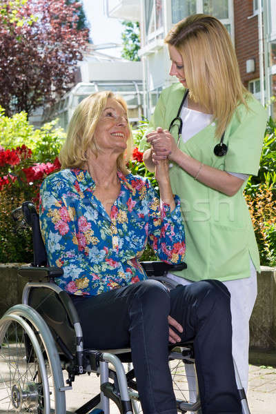 Nurse Holding Hands with Senior Woman in Garden Stock photo © belahoche