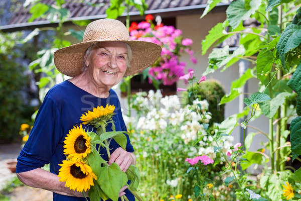 Glimlachend oude vrouw zonnebloemen tuin gelukkig Stockfoto © belahoche