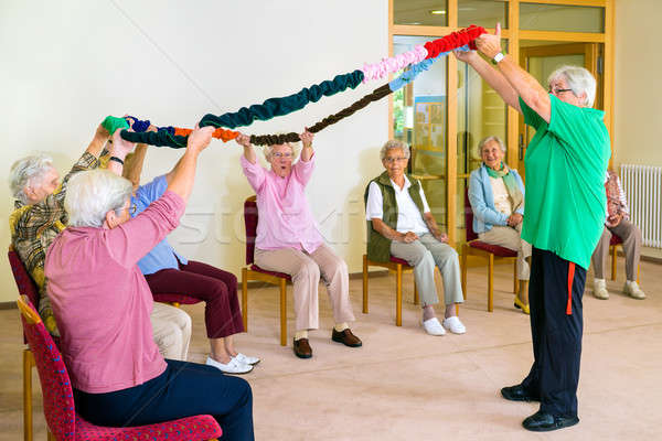 Trainer lifting garland for class with seniors Stock photo © belahoche