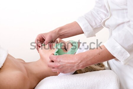 Masseuse massaging a woman eyebrow area.  Stock photo © belahoche
