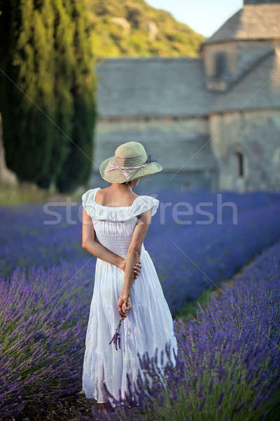 Stock photo: Young woman in lavender field looking to the medieval Abbey of S