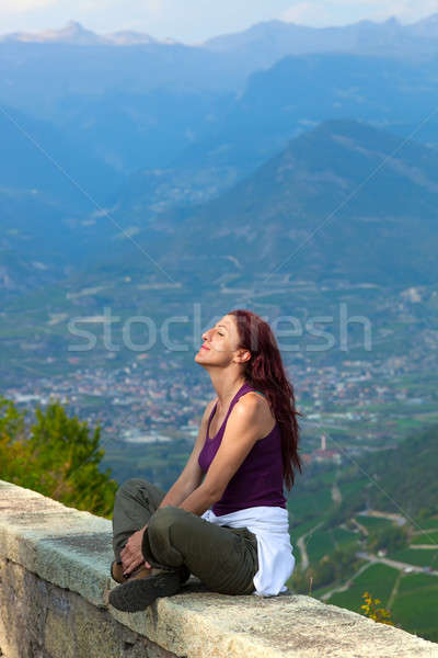 Woman with eyes closed sitting on a ledge. Stock photo © belahoche