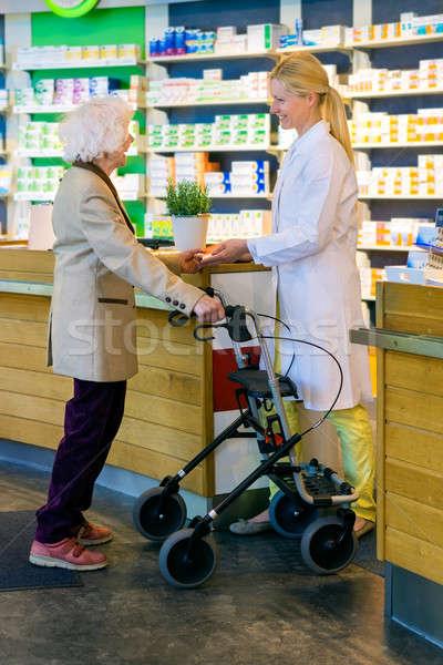 Elderly customer using walker with pharmacist Stock photo © belahoche