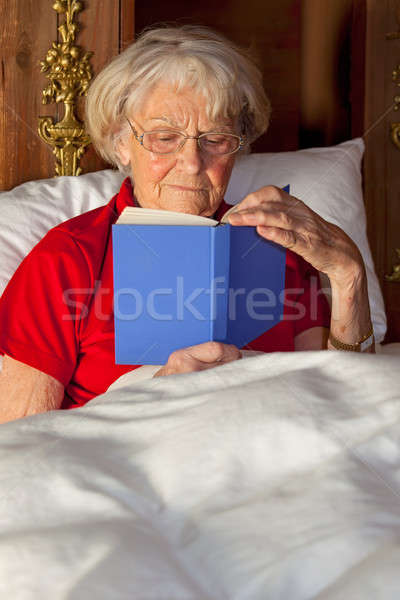 Elderly woman reading in bed Stock photo © belahoche