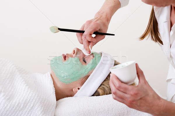 Beautician retouching a blond woman thalasso facial mask.  Stock photo © belahoche