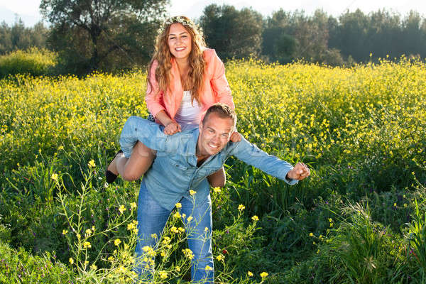 Playful young couple riding piggy back Stock photo © belahoche