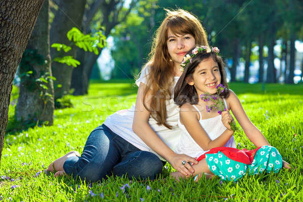 Beautiful young girl with her mother on lush grass Stock photo © belahoche