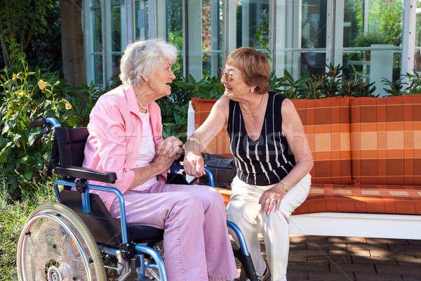 Two senior ladies chatting on a garden bench Stock photo © belahoche