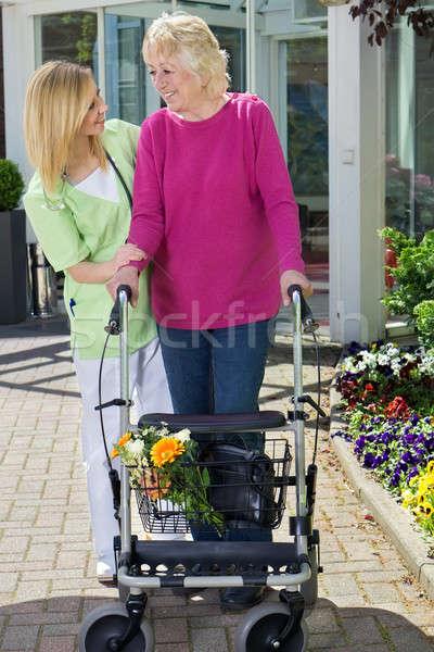 Nurse Helping Senior Woman to Walk with Walker Stock photo © belahoche