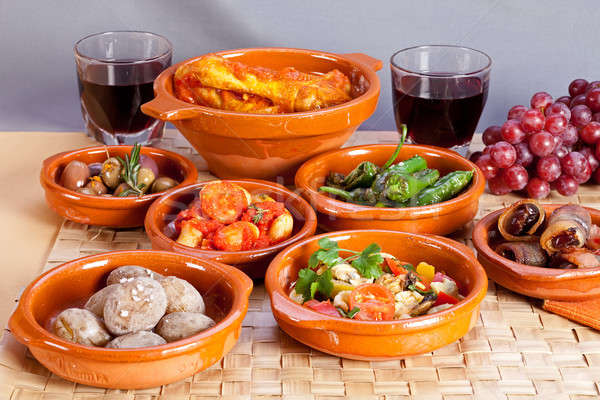 Collection of spanish tapas foods in terracotta bowls. Stock photo © belahoche