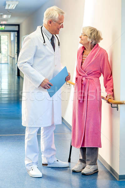 Doctor talking to an elderly woman in the corridor.  Stock photo © belahoche