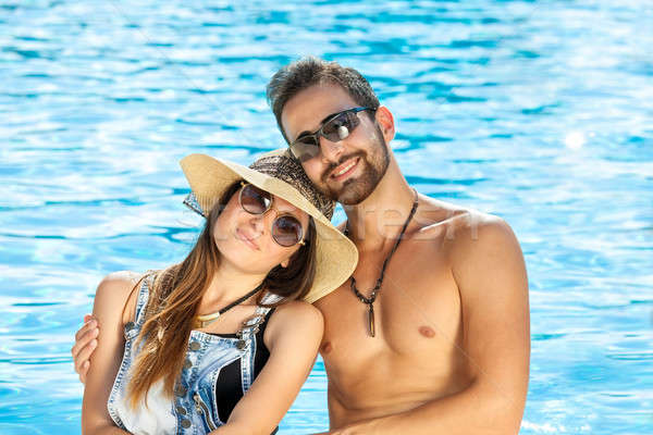 Affectionate happy couple relaxing at a pool Stock photo © belahoche
