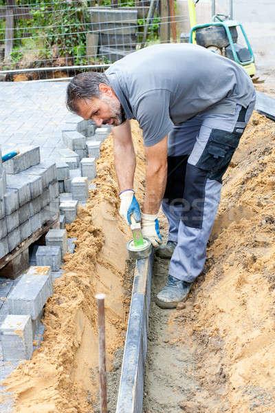 Worker puts border stones. Stock photo © belahoche