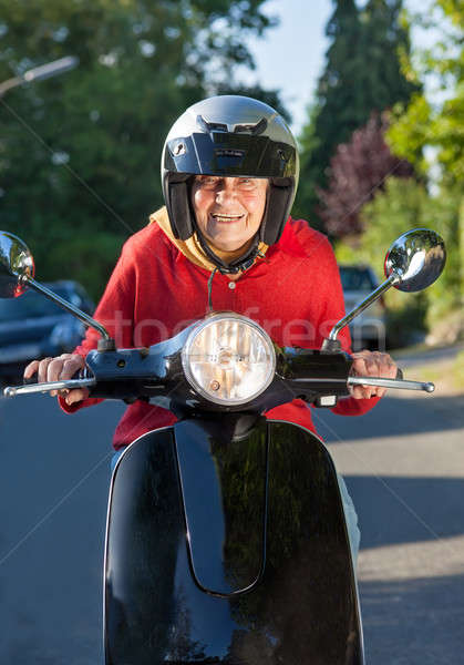 Laughing senior woman riding a scooter Stock photo © belahoche