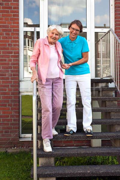 Barátságos gondozó segít idős hölgy lépcső Stock fotó © belahoche