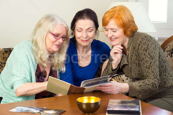 Middle Age Female Friends Looking at Photo Album Stock photo © belahoche
