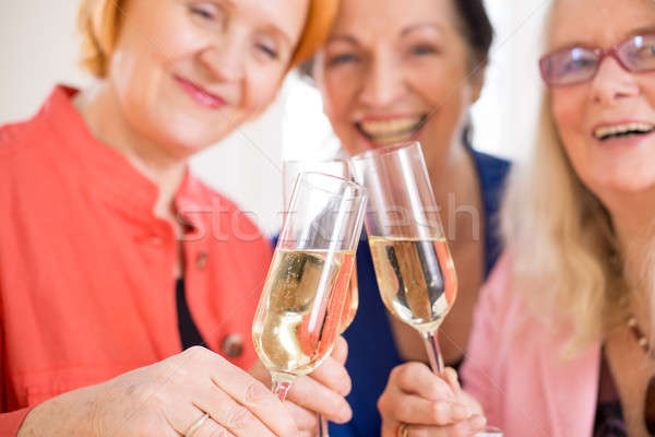 Smiling Mom Friends Tossing Glasses of Champagne Stock photo © belahoche