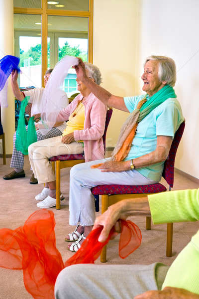 Enthusiastic women doing exercises in chairs Stock photo © belahoche