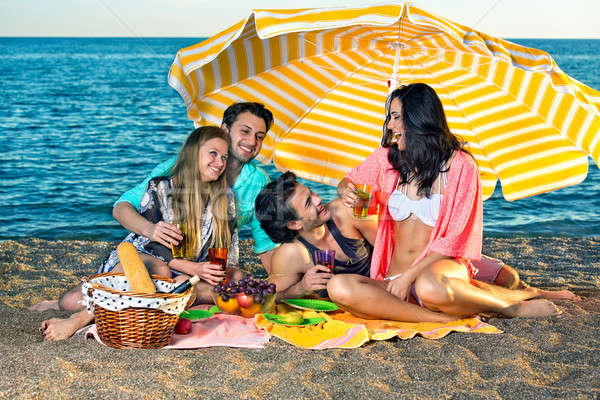 Four carefree friends seated under yellow umbrella Stock photo © belahoche