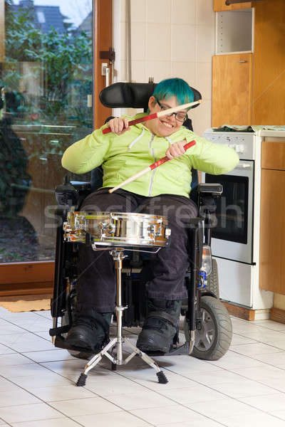 Stock photo: Young woman with cerebral palsy playing a drum