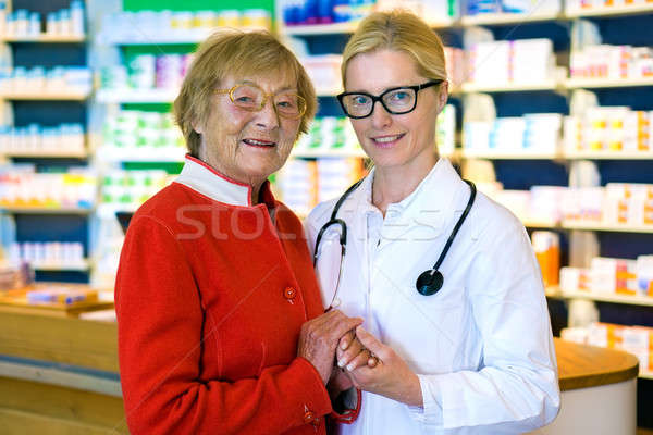 Happy doctor with female patient in pharmacy Stock photo © belahoche