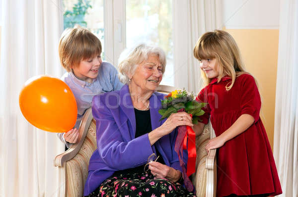 Grandma receives flowers from grand kids Stock photo © belahoche