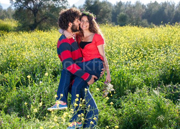 Happy young man carrying his beautiful girlfriend Stock photo © belahoche