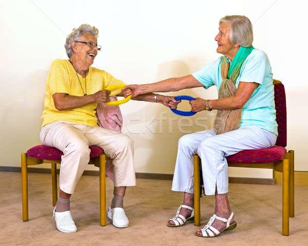 Senior women doing partner stretches Stock photo © belahoche