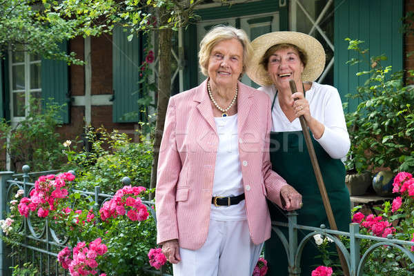 Two Senior Women Standing Together in Garden Stock photo © belahoche