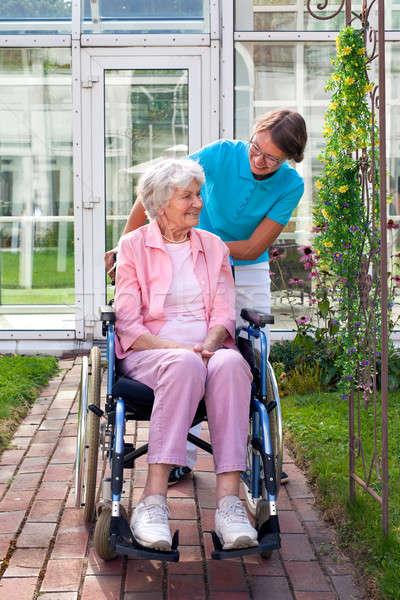 Souriant heureux supérieurs dame fauteuil roulant marche Photo stock © belahoche