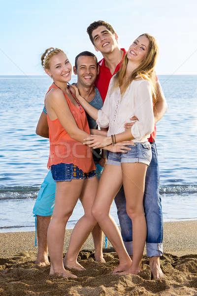 Fiatal barátok élvezi tengerpart teljes alakos néz Stock fotó © belahoche