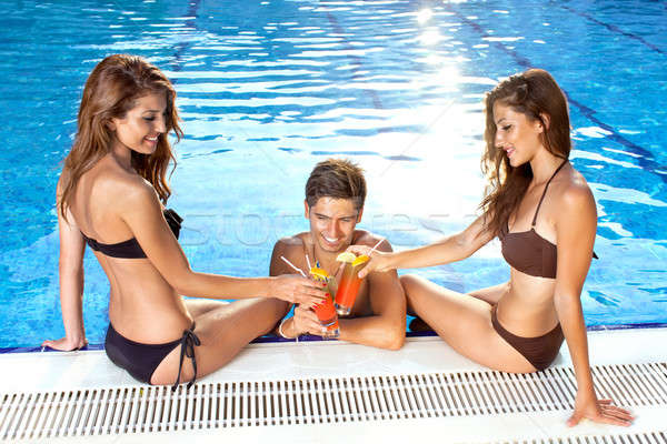 Three friends toasting each other at the pool Stock photo © belahoche