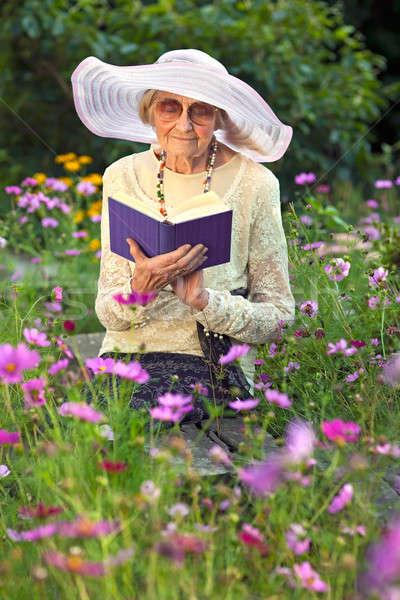 Elegant elderly lady reading in her garden Stock photo © belahoche